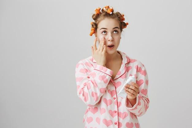 Linda garota com rolos de cabelo e pijama aplica creme facial