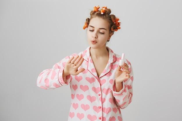 Linda garota com rolos de cabelo no cabelo e pijama, esmalte de unhas