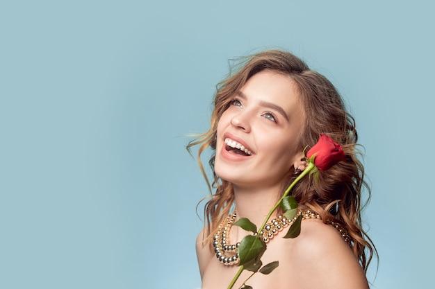 Linda garota com rosa vermelha e joias de pérolas - brincos, pulseira, colar na parede azul.