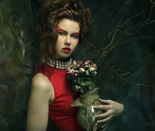Linda garota com rosas secas em decoração gótica