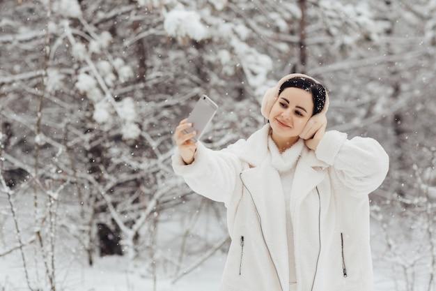 Linda garota com roupas brancas e fones de ouvido fofos, tomando selfie com smartphone ao ar livre em dia de neve de inverno.