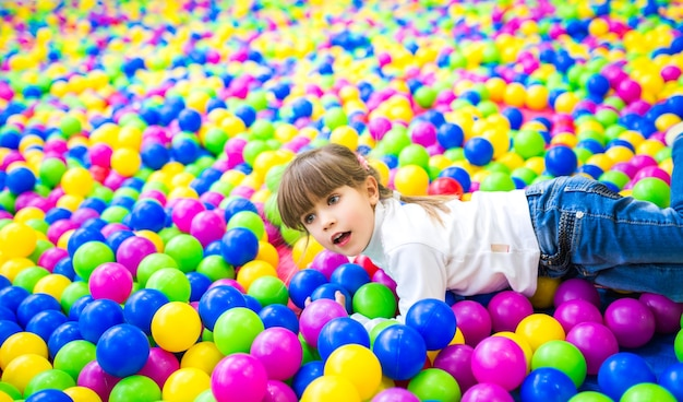 Linda garota com roupas de criança brinca na piscina com bolas de plástico brilhantes de cores diferentes