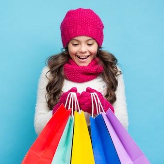 Linda garota com roupas de inverno e sacolas de compras