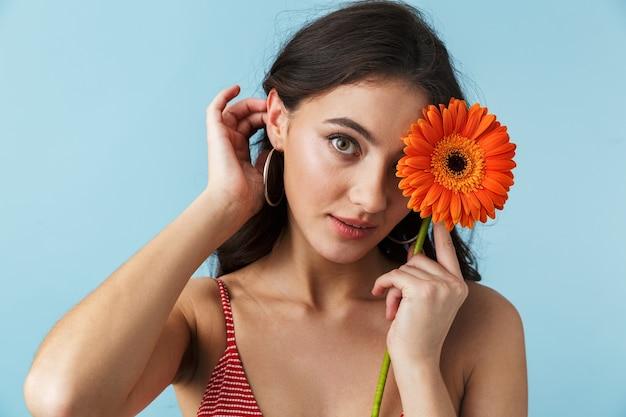 Linda garota com roupas de verão em pé isolada sobre o azul, posando com uma flor herbera
