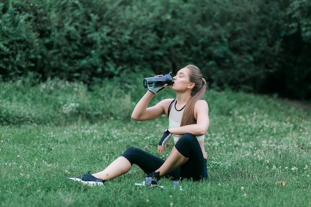 Linda garota com roupas esporte, beber água depois de treino enquanto está sentado na grama
