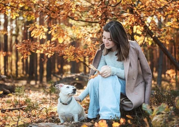 Linda garota com seu cachorro na floresta. floresta de outono.
