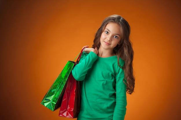 Linda garota com suéter verde com sacolas de compras