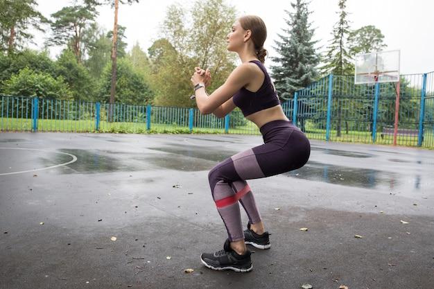 Linda garota com top esportivo e legging treina com corda elástica vermelha em quadras esportivas no parque