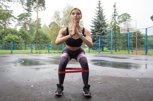 Linda garota com top esportivo e legging treina com corda elástica vermelha no parque