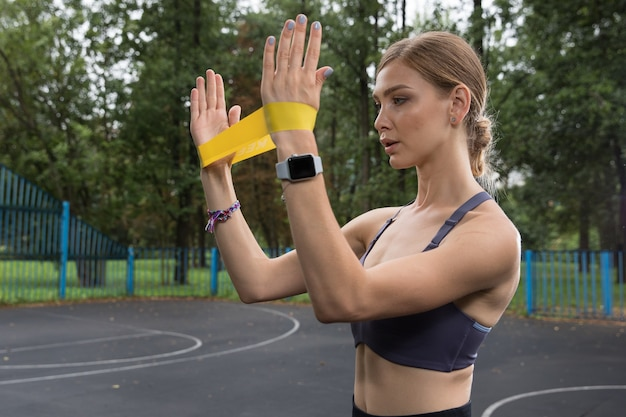 Linda garota com top esportivo e leggings treina com corda elástica amarela em quadras esportivas no parque