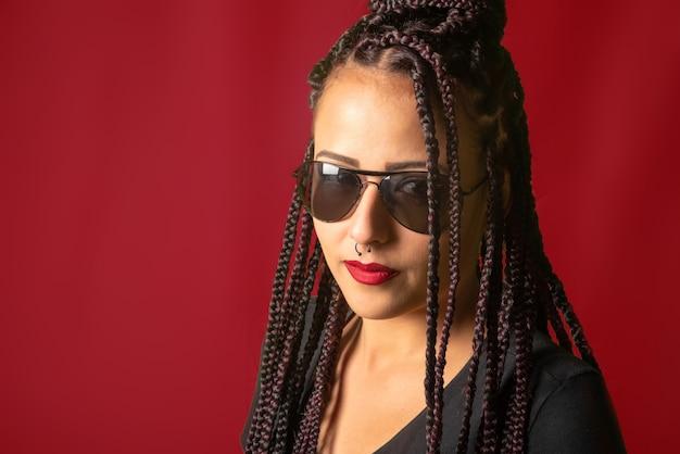 Linda garota com tranças no cabelo e óculos escuros