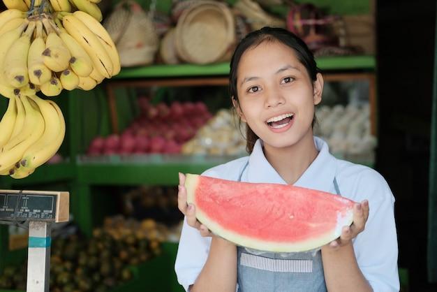 Linda garota com um avental carregando uma melancia em uma barraca de frutas, conceito de frutas frescas