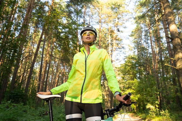 Linda garota com um blusão verde brilhante, shorts, óculos e capacete, descansando após andar de bicicleta na floresta