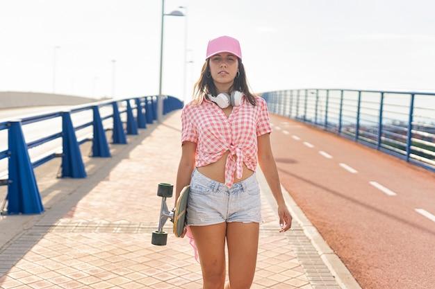 Linda garota com um boné no cabelo rosa e fones de ouvido caminha com seu skate nas ruas da cidade