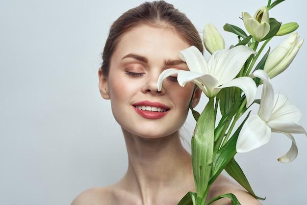 Linda garota com um buquê de flores brancas sobre um fundo claro, ombros nus, pele limpa