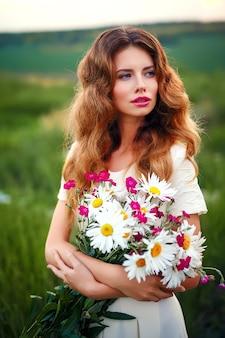 Linda garota com um buquê de flores de camomila branca