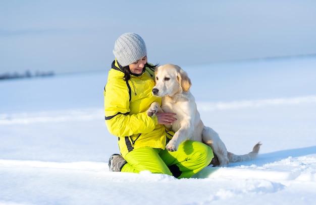 Linda garota com um cachorro adorável lá fora no inverno