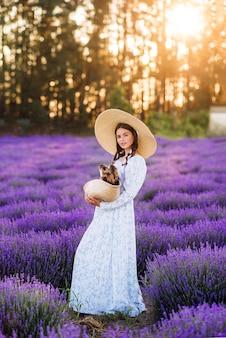 Linda garota com um cachorro em uma cesta em lavanda. ela está usando um vestido longo e um chapéu grande ..