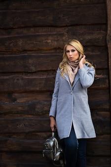 Linda garota com um casaco cinza. na rua. outono.