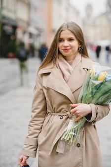 Linda garota com um casaco marrom. mulher em uma cidade de primavera. senhora com buquê de flores