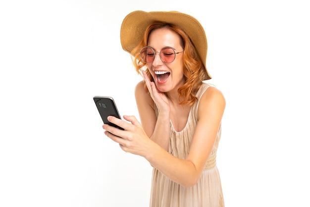 Linda garota com um chapéu de verão e óculos escuros compra os ingressos pelo telefone