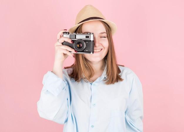 Linda garota com um chapéu e uma camisa azul tira uma foto em uma câmera velha em um fundo rosa