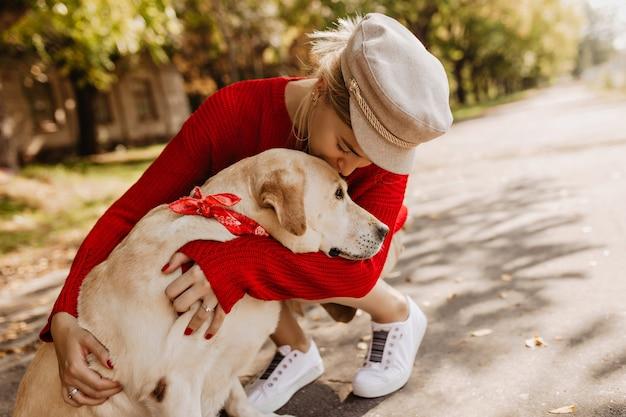 Linda garota com um chapéu estiloso e tênis branco, segurando seu cachorro com ternura. loira linda sentada com seu animal de estimação no parque.