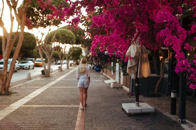 Linda garota com um chapéu nas costas caminhando por um beco florido