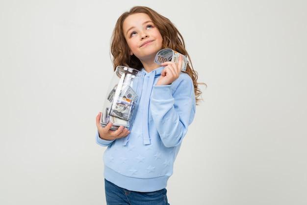 Linda garota com um frasco de vidro e dinheiro em uma parede branca.