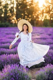 Linda garota com um grande chapéu e um vestido completo em um fundo de lavanda. uma jovem modelo com tranças no cabelo. foto de verão ao sol.