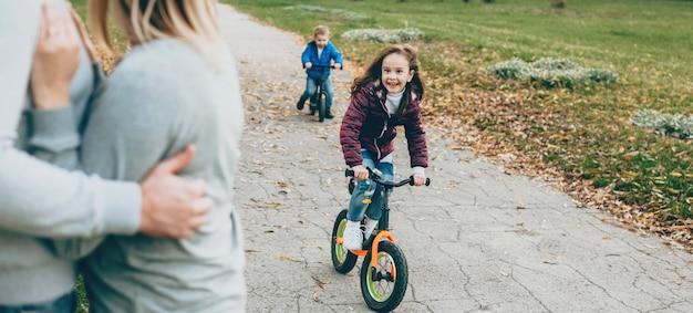 Linda garota com um irmãozinho andando de bicicleta no parque enquanto os pais os observam