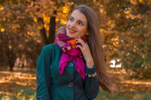 Linda garota com um lenço rosa em volta do pescoço está no parque e sorri