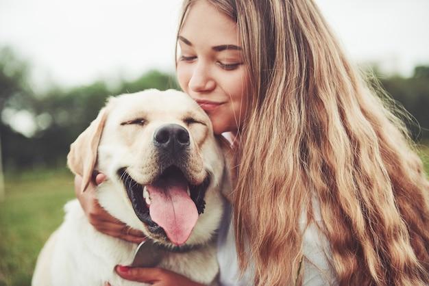 Linda garota com um lindo cachorro em um parque na grama verde.