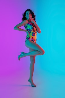 Linda garota com um maiô elegante isolado no fundo do estúdio gradiente em luz de néon