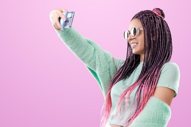 Linda garota com um penteado de tranças cor de rosa em roupas turquesa, posando em um fundo rosa no estúdio. o conceito é estilo moderno, individualidade, abrangência, criatividade.