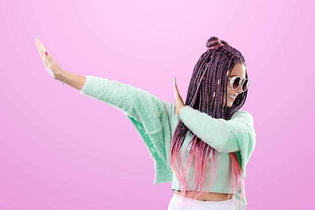 Linda garota com um penteado de tranças cor de rosa em roupas turquesas e óculos escuros posando em um fundo rosa no estúdio. o conceito é estilo moderno, individualidade, abrangência, criatividade.