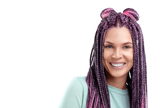 Linda garota com um penteado de tranças cor de rosa em roupas turquesas, sorrisos e poses em um fundo branco no estúdio. o conceito é estilo moderno, individualidade, abrangência, criatividade.