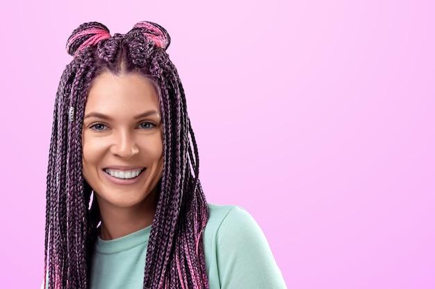 Linda garota com um penteado de tranças cor de rosa em roupas turquesas, sorrisos e poses em um fundo rosa no estúdio. o conceito é estilo moderno, individualidade, abrangência, criatividade.