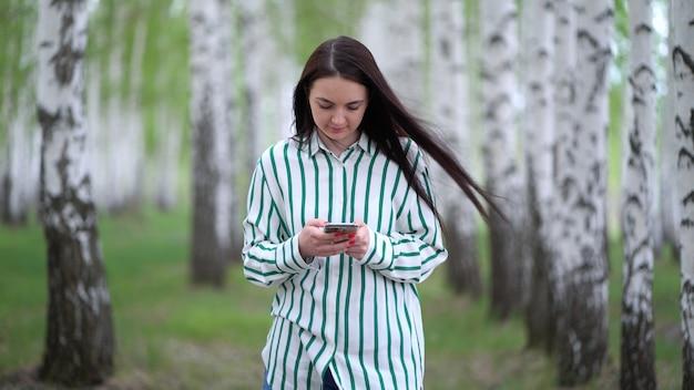 Linda garota com um smartphone nas mãos caminha ao longo de um bosque de bétulas na primavera