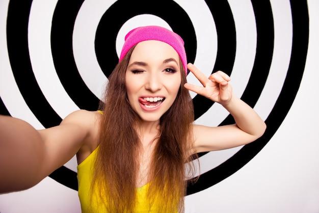 Linda garota com um sorriso radiante em boné rosa fazendo selfie e piscando