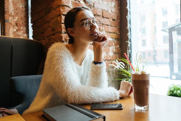 Linda garota com um suéter branco e óculos está sentada em um café e olha pensativamente pela janela