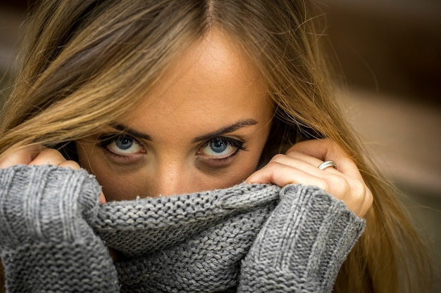 Linda garota com um suéter com cabelo comprido e lábios vermelhos na parede de toras de madeira