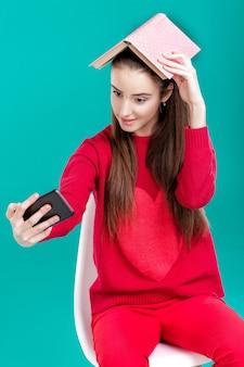 Linda garota com um suéter vermelho lê um livro e usa um smartphone para selfie