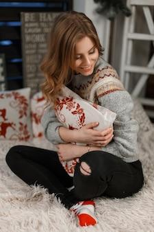 Linda garota com um suéter vintage da moda abraça um travesseiro e se senta na cama