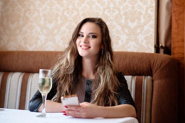 Linda garota com um telefone em uma mesa no restaurante.