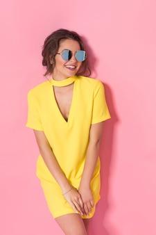 Linda garota com um vestido amarelo posando de óculos escuros, sorrindo no espaço rosa no estúdio