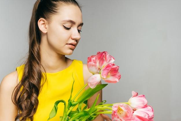 Linda garota com um vestido amarelo segurando um grande buquê de flores cor de rosa, comemora