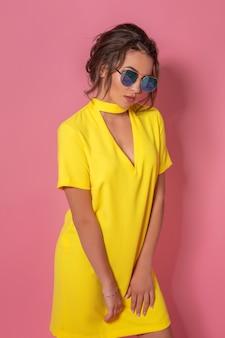 Linda garota com um vestido amarelo usando óculos escuros posando sorrindo no fundo rosa