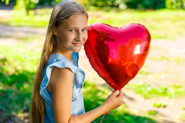 Linda garota com um vestido azul e um balão em forma de coração