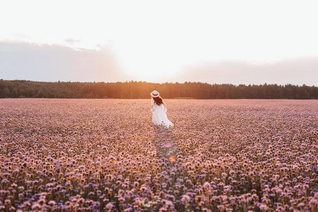Linda garota com um vestido branco em um campo de lavanda ao pôr do sol